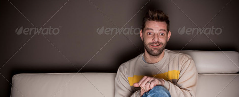 A man with crossed legs watching TV